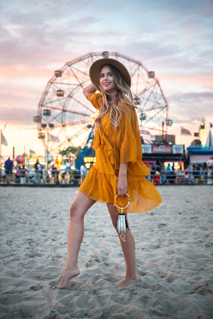 Woman in yellow dress and wide brim hat exploring carnival on the beach.