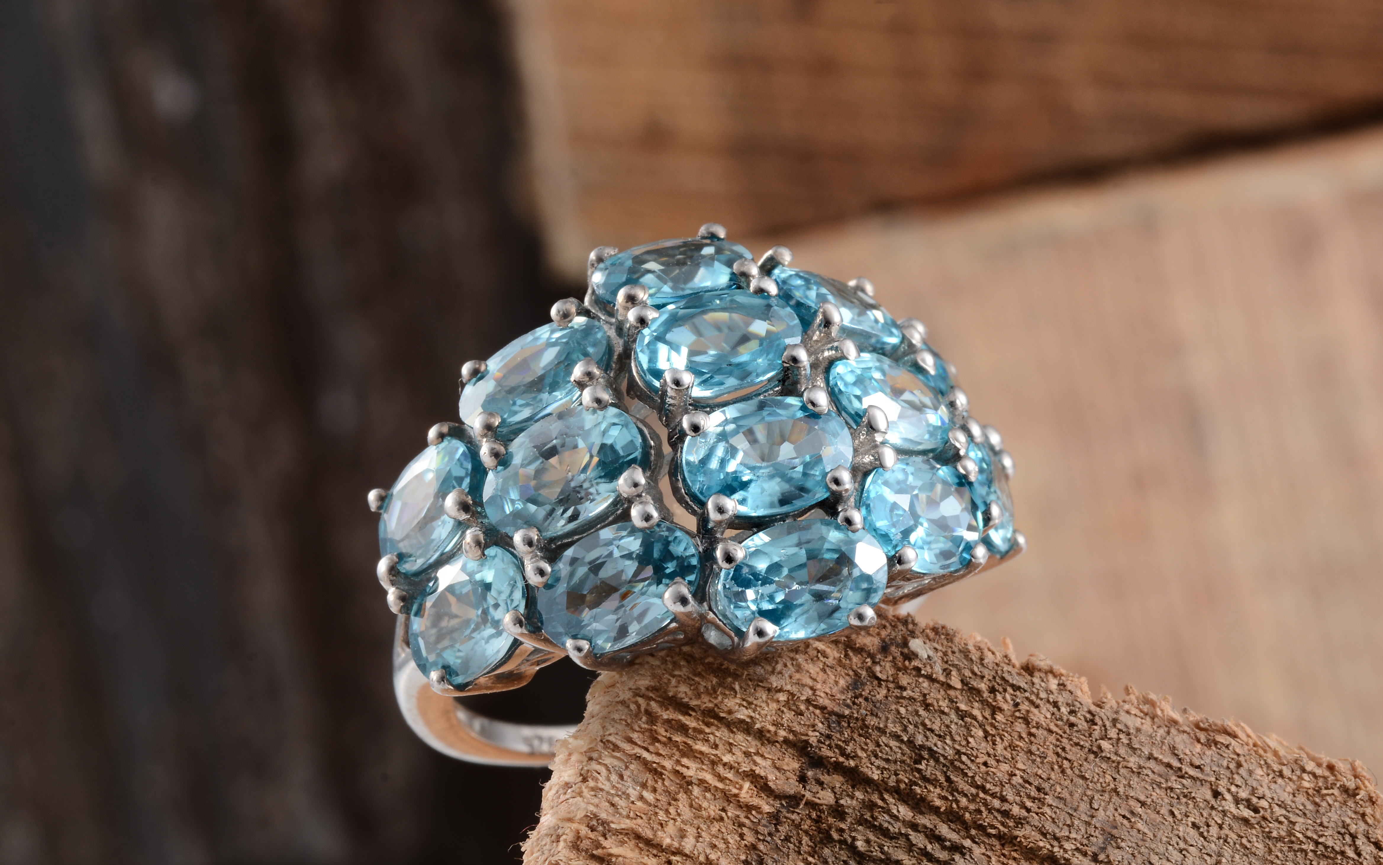 Blue zircon cluster ring on wooden stand.