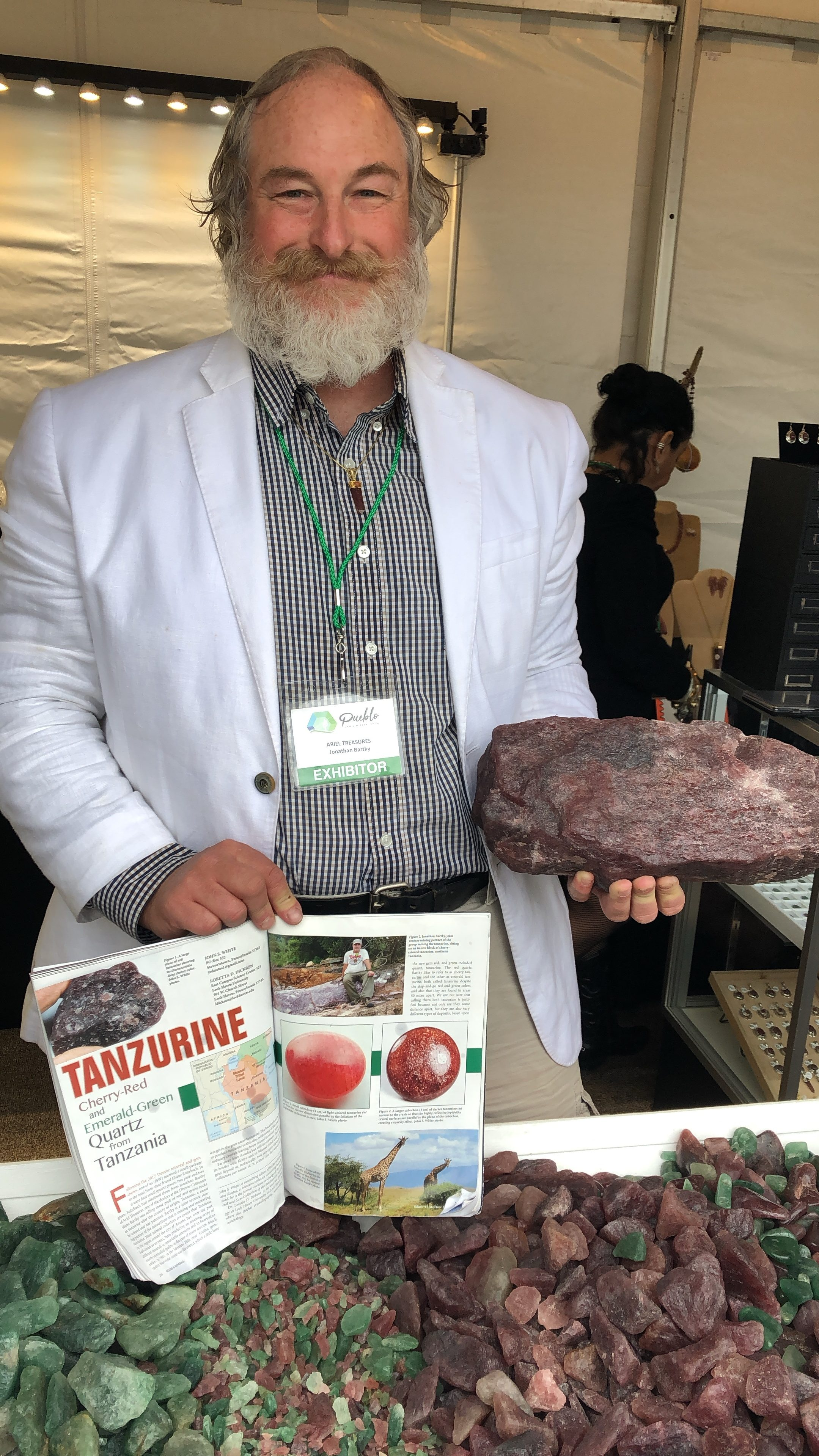 Jonathan Bartky holding large specimen of cherry tanzurine at gem show.