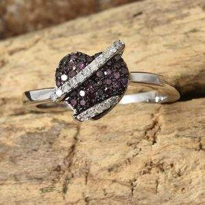 Heart-shaped purple diamond ring on wood base.