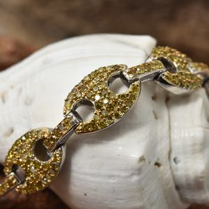 Close up on yellow diamond bracelet draped over shell.
