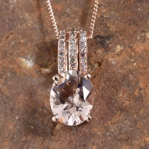 Morganite and pink diamond pendant resting on stone.