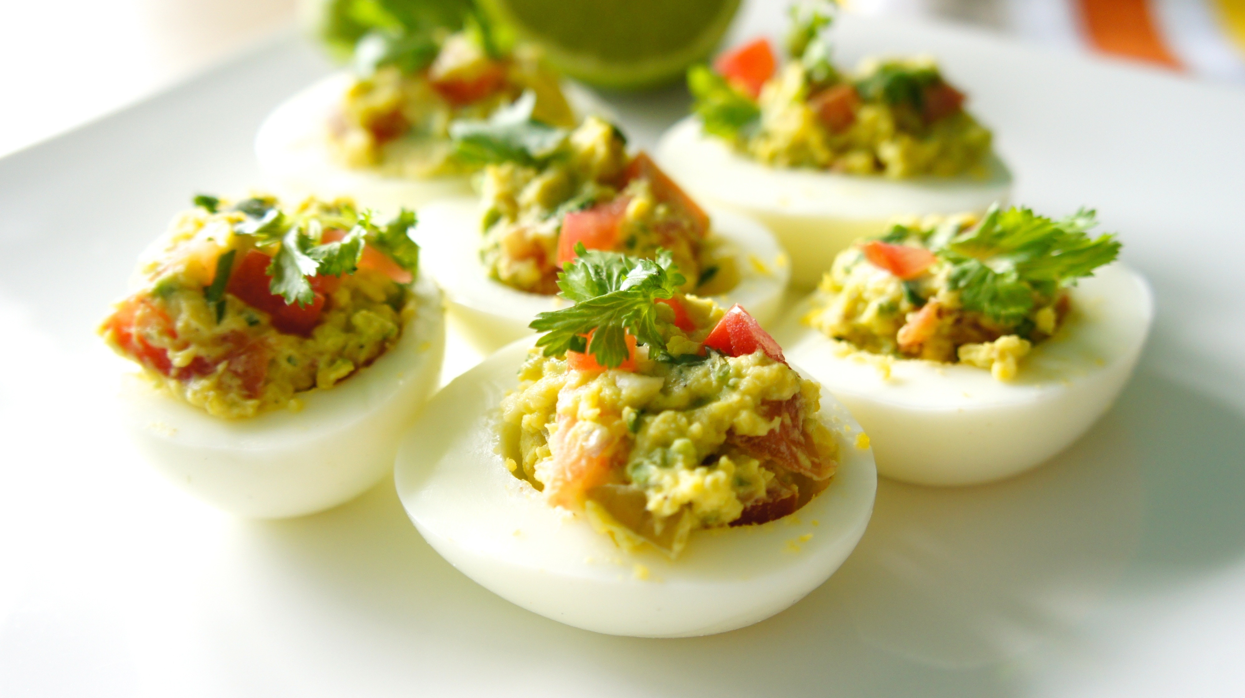 Avocado deviled eggs with garnish.