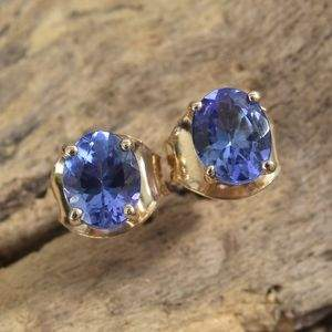 AAA tanzanite stud earrings in 14K gold on wood display.