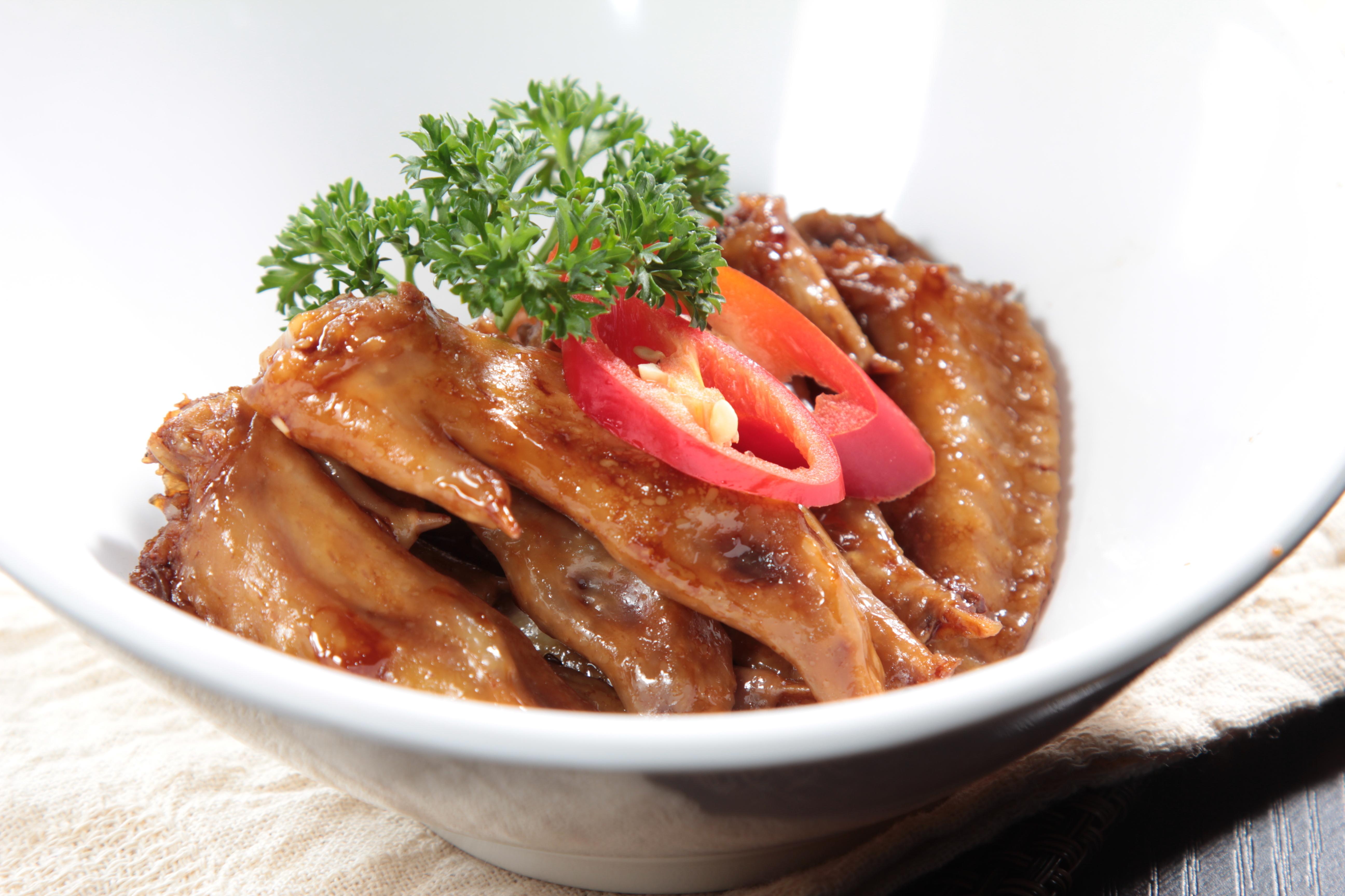 Dish of braised chicken with garnish.