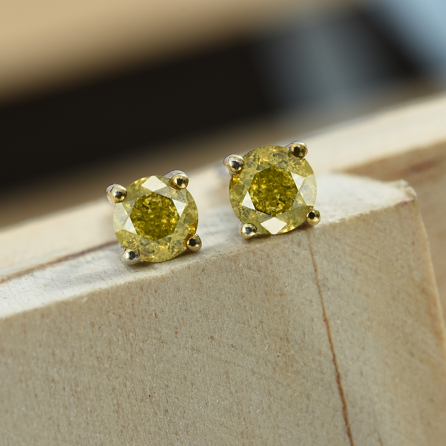Yellow diamond stud earrings displayed on wooden plinth.