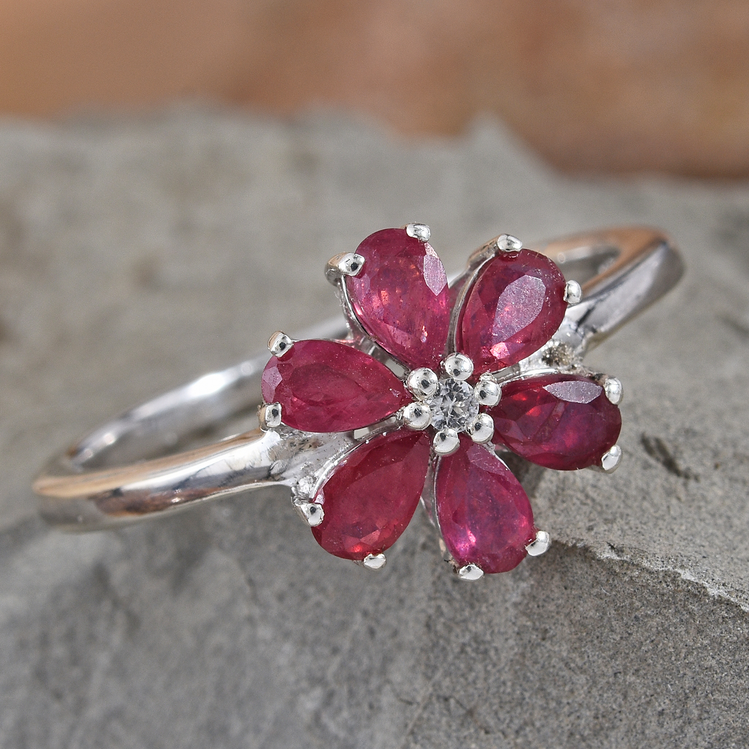 Floral ruby ring daintily resting on granite display.