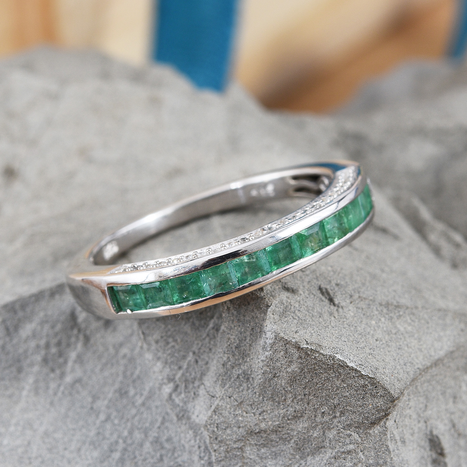 Emerald ring with channel set stones resting on slate.