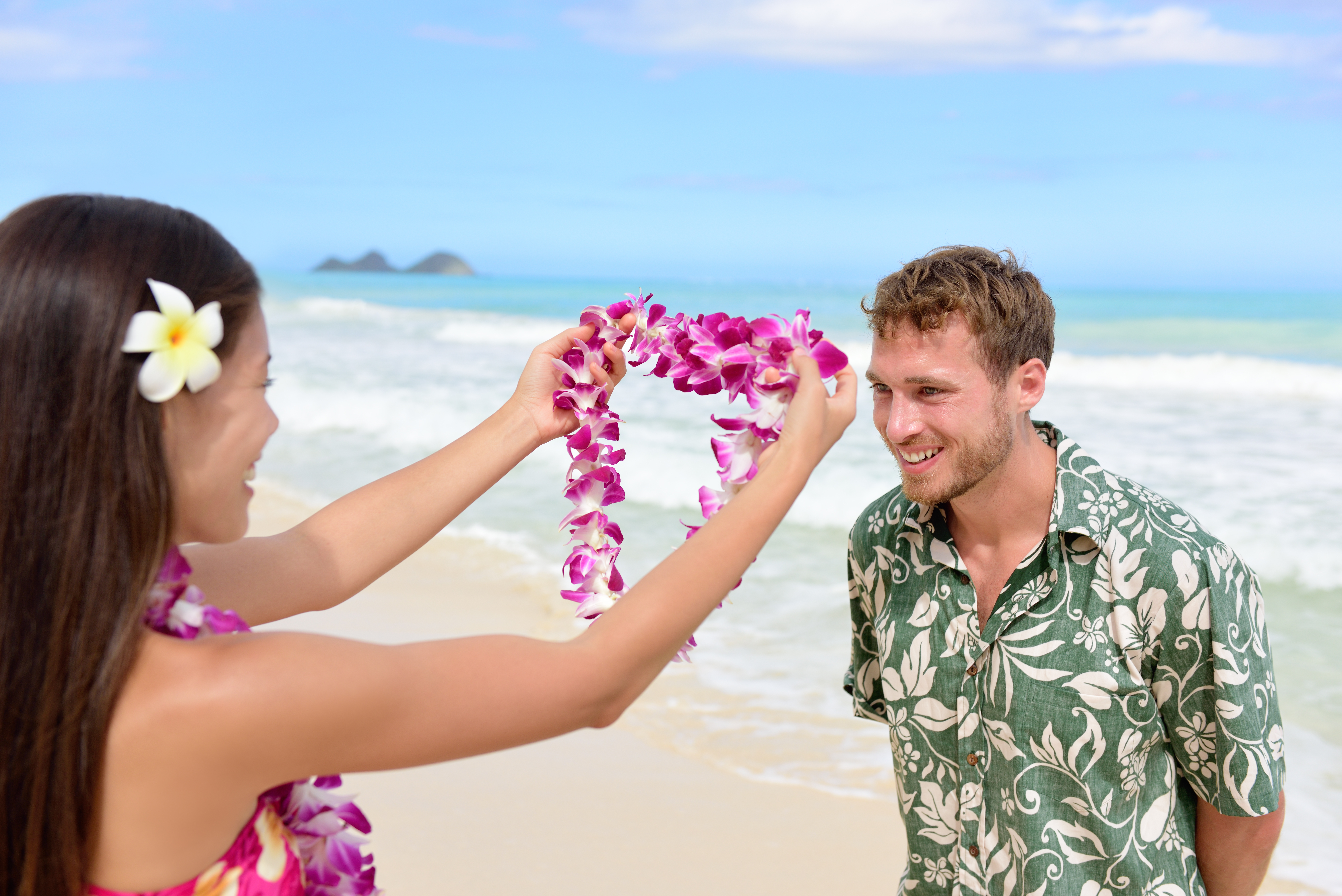 Hawaiian woman presenting a lei to a visitor on the beach.