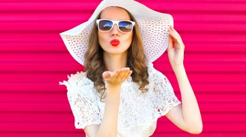 Woman in white outfit with white summer hat, blowing kisses.