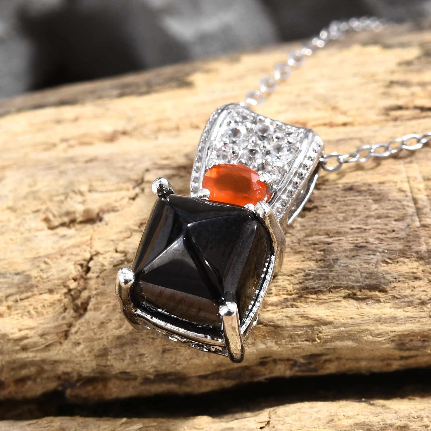 Shungite pendant with carnelian accent displayed on drift wood.
