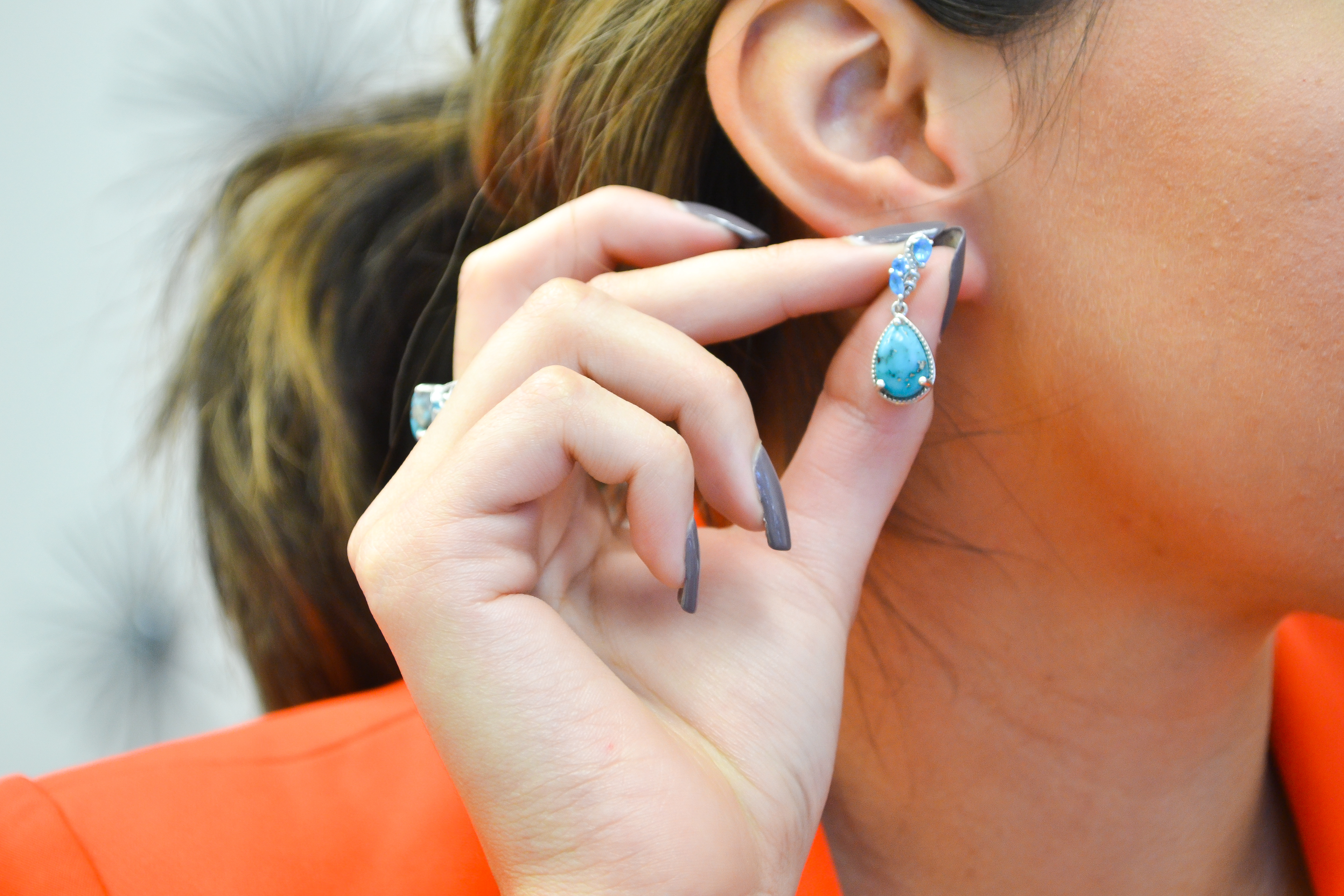 Woman in coral blazer trying on turquoise earrings.