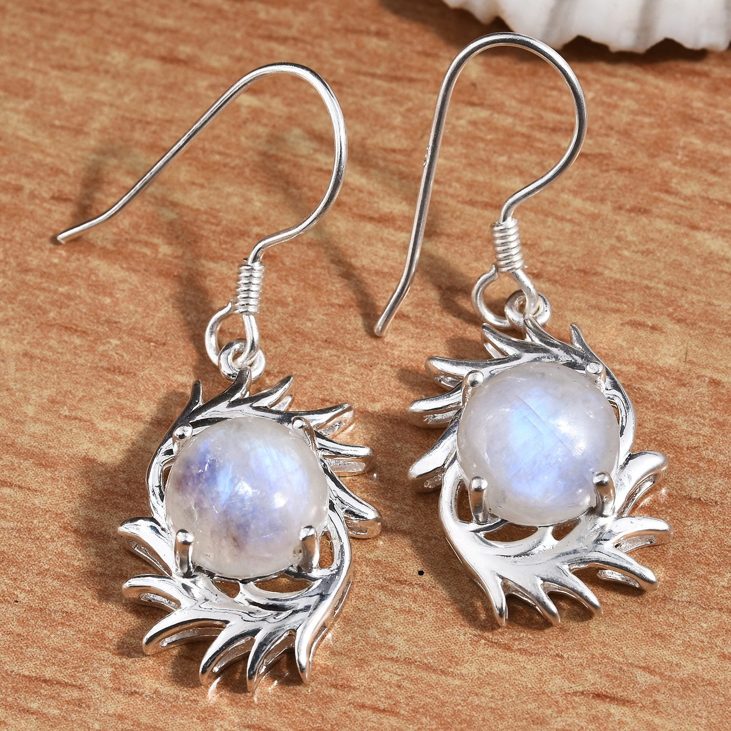 Moonstone earrings displayed on wooden board.