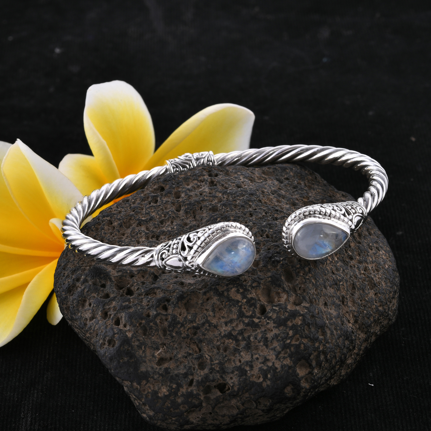 Moonstone bangle perched on lava rock.