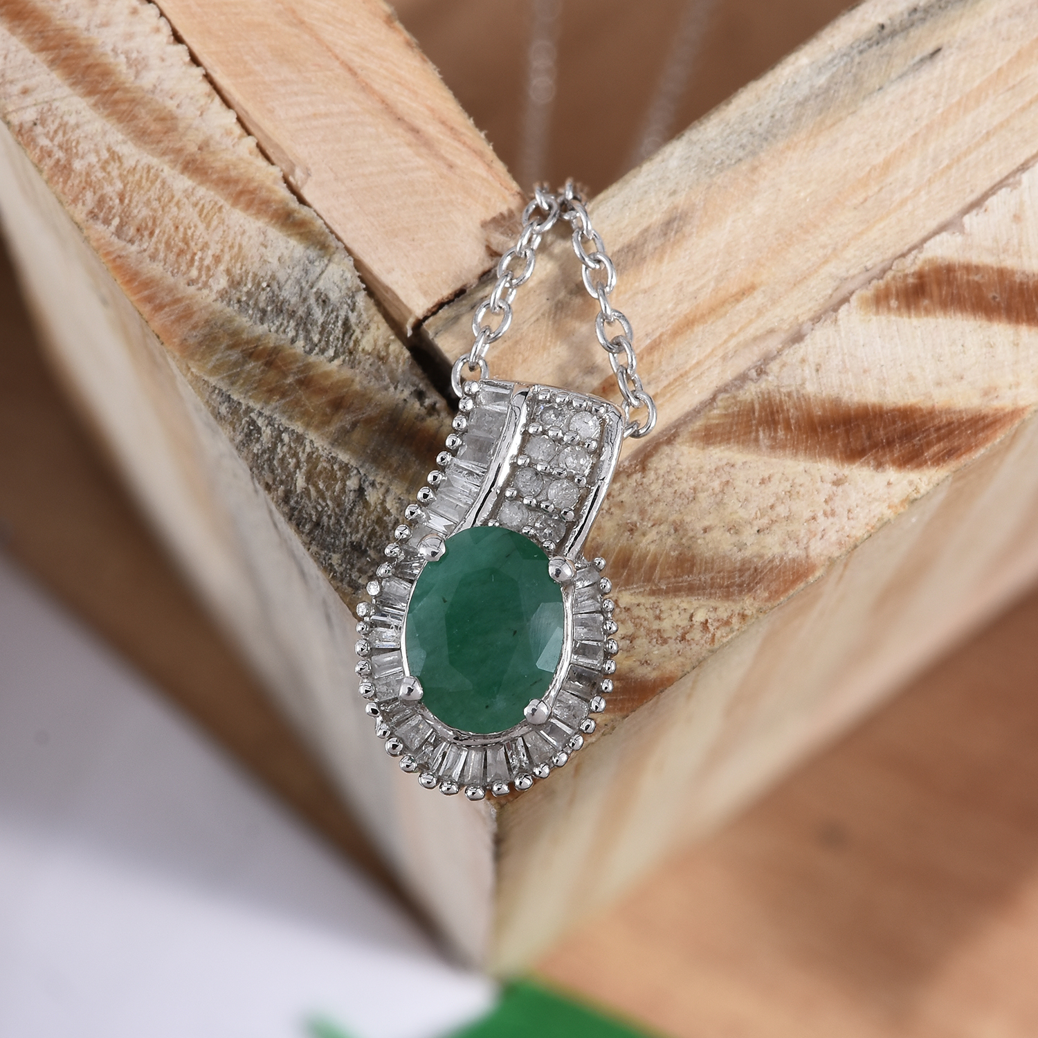 Emerald pendant draped over wooden frame.