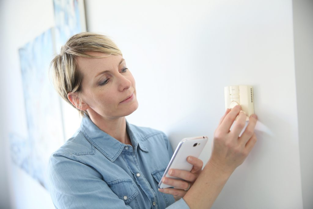Woman adjusting her thermostat.