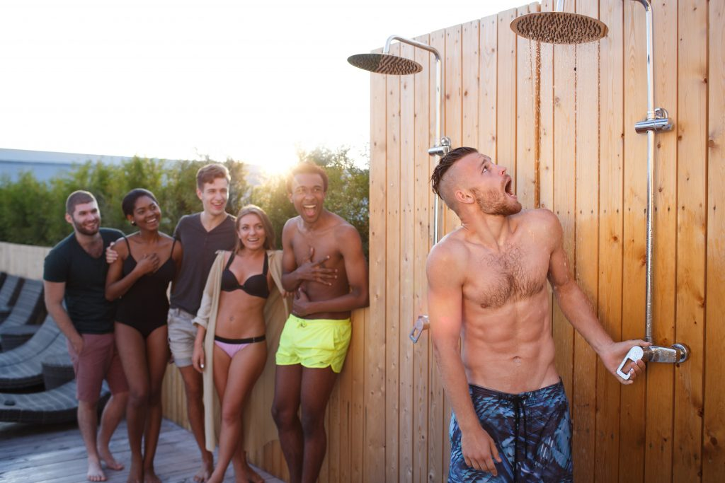Group of friends hitting the showers after swimming at the pool.