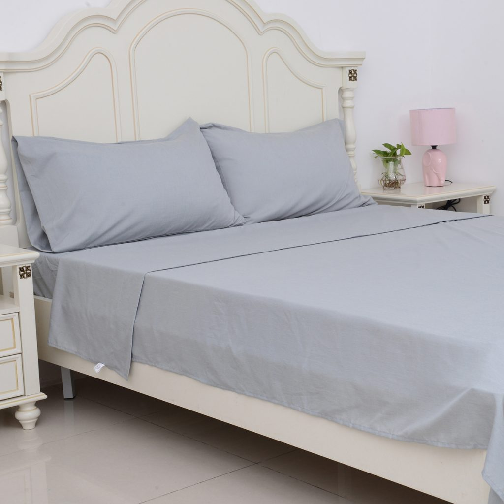 Bed fitted with gray bamboo sheets.