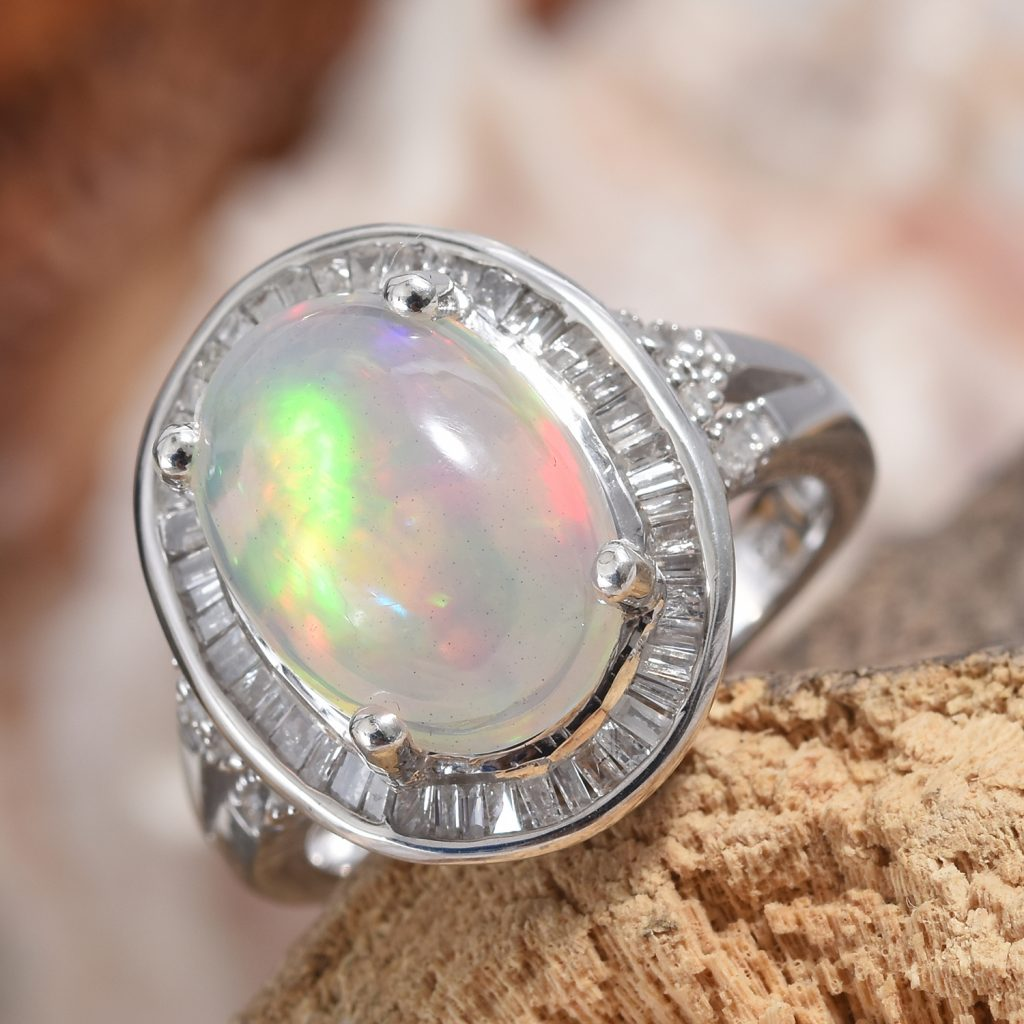 Welo opal halo ring in sterling silver on natural display.