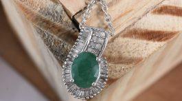 Socoto Emerald pendant draped over wood.