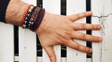 Man's wrist with bracelets against white wooden background.