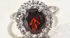 Mozambique garnet ring on textured white background.