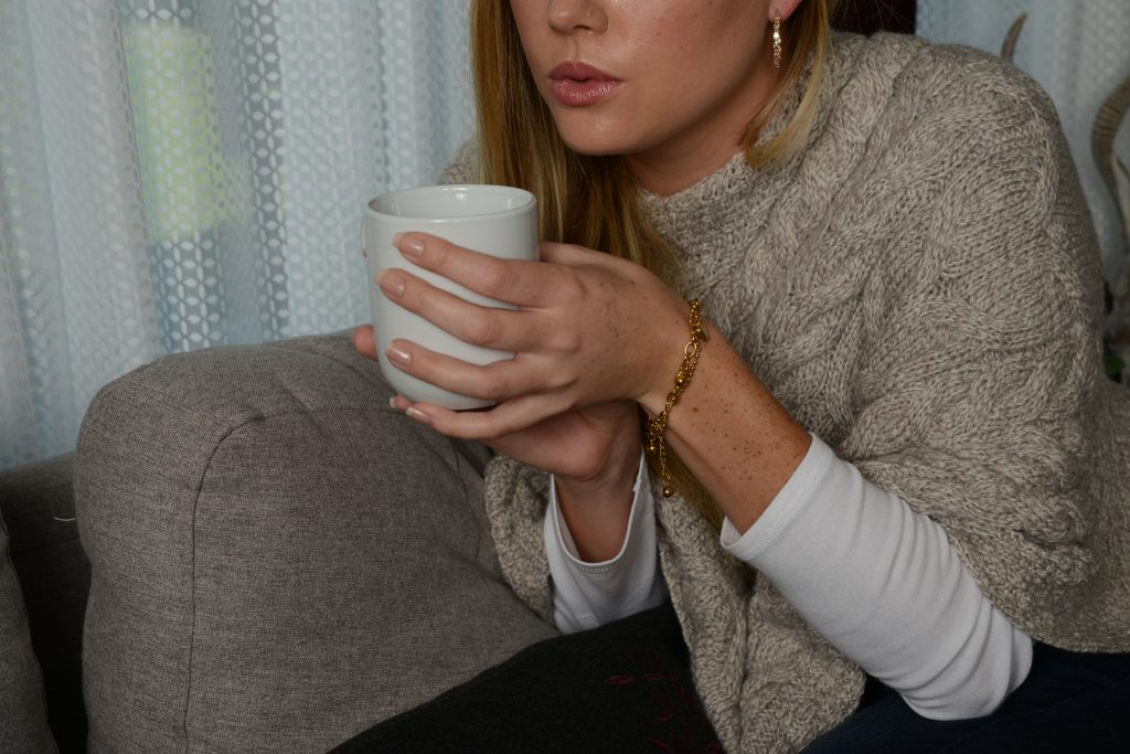 Blonde woman holding cup on coffee.