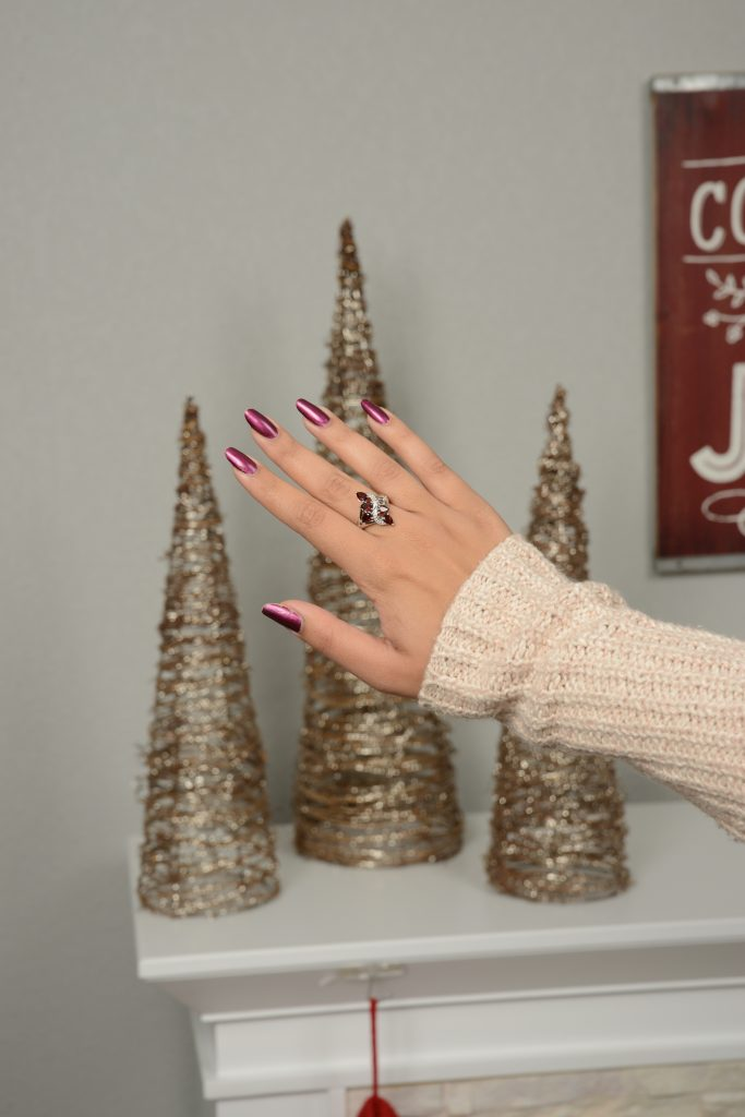 Woman admiring ring in front of holiday decorations.