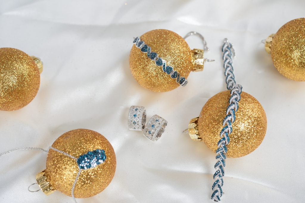 Flay lay of jewelry with Christmas ornaments.