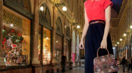Woman posing with Signare handbag on nighttime street.