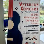 Sign for the Veterans Concert, sponsored by Shop LC.