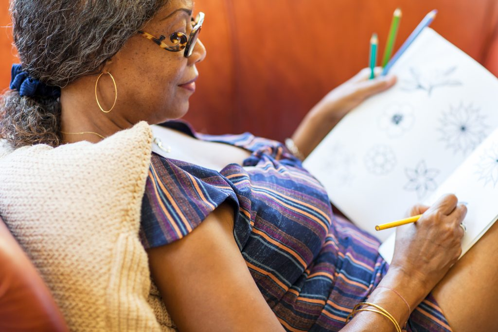 Senior woman coloring in an adult coloring book.