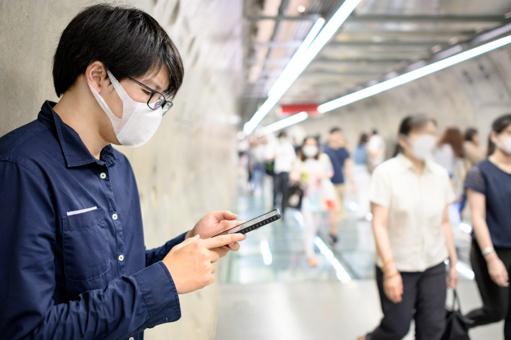 Asian man wearing surgical face mask using smartphone in subway tunnel with crowded people walking.