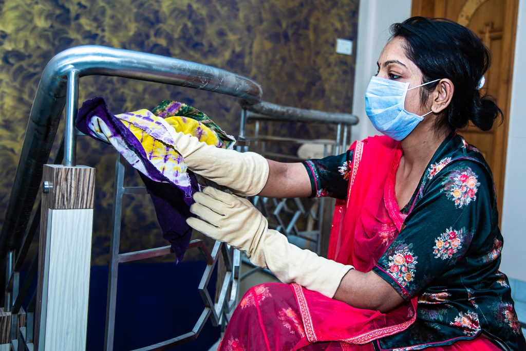 Indian woman with face mask cleaning and disinfecting her house during coronavirus epidemic.