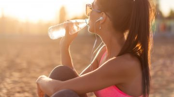 Woman drinking water on beach after workout.