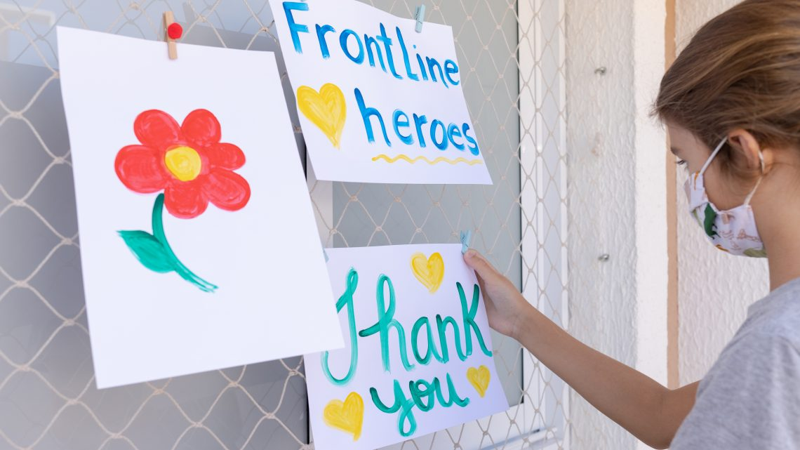 Child hanging thank you message for frontline workers.