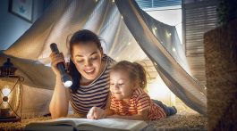 Mother and child reading a book in a blanket fort.