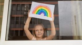 Little girl holding up rainbow she painted during coronavirus pandemic.