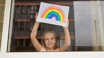 Little girl holding up rainbow she painted during coronavirus pandemic.