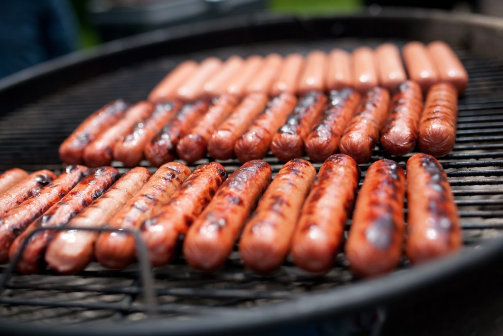 Cooking franks on a charcoal grill.